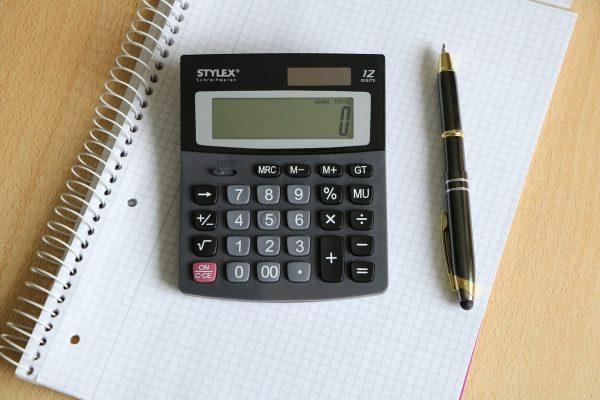A calculator and pen atop an A4 notebook