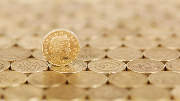 A perfectly flat surface of pound coins, with a single pound coin sitting atop them on its side