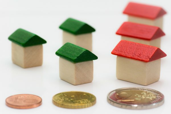 six monopoly houses, with three coins in front