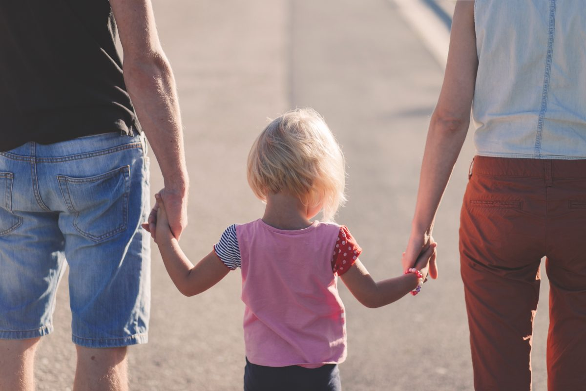 A child walking between their parents, holding both their hands
